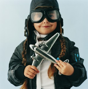 Young Girl in an Aviator Costume Folding a Toy Aircraft